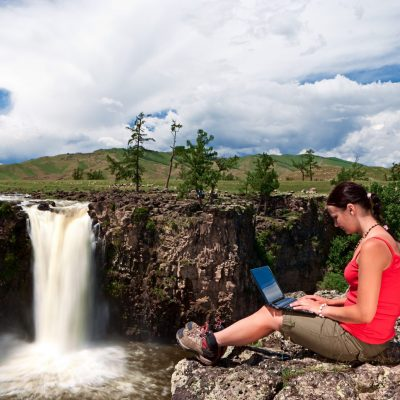A young womanl sitting on a rock and using laptop. Waterfall on the background.http://bem.2be.pl/IS/outdoors_laptop_380.jpg